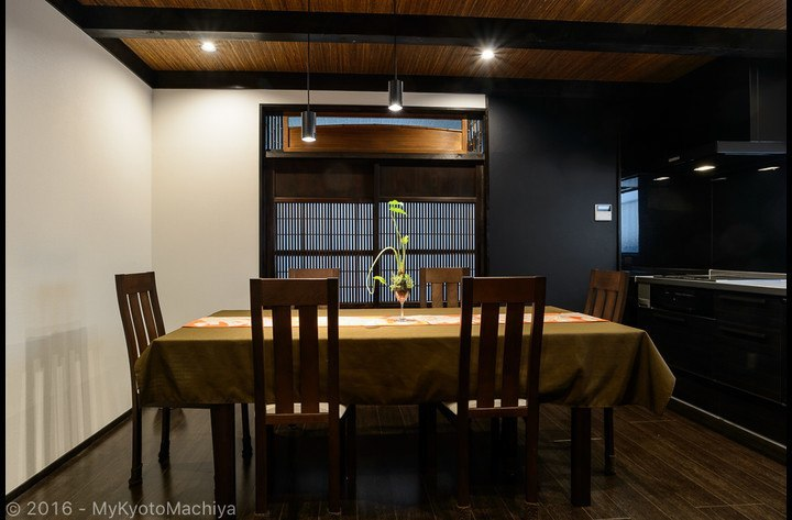 Modern dining area with 100 year old wooden door to access the bathroom
