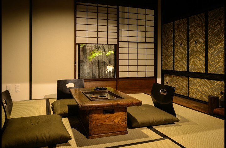 The Japanese living room with the Tsuboniwa garden behind paper windows. A large screen TV is hidden behind the fusuma doors on the right.