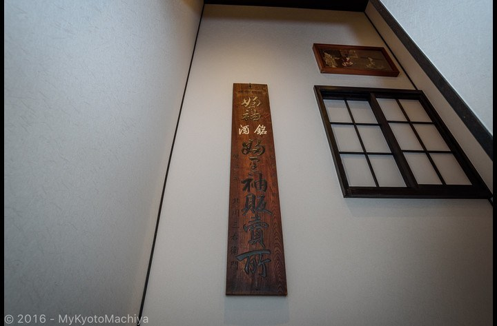 An old panel of a Sake Brewery is used to decorate the stairs well.